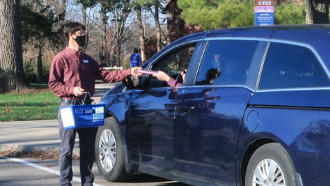 patron has curbside delivery item handed to their car by librarian