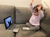 toddler holding hands up like the librarian on her laptop is