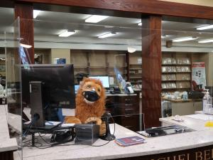 masked stuffed lion at research desk